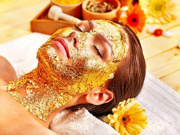 woman-getting-facial-mask-gold